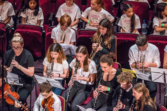 A group in one of our orchestras playing clarinet, oboe, trumpet and violin. Some children are seated on red chairs behind them.