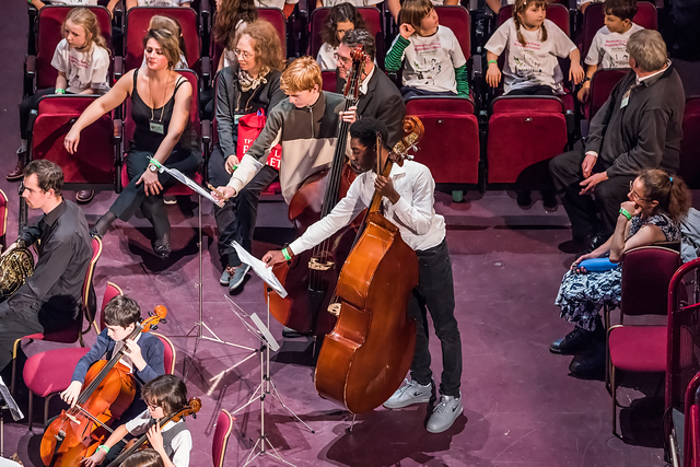 Two of our students are standing holding double basses and reaching to turn the music on their music stands. Further orchestra members are to their left. Other children taking part in the concert and some of our tutors, parents and trustees are behind and to the right of them.