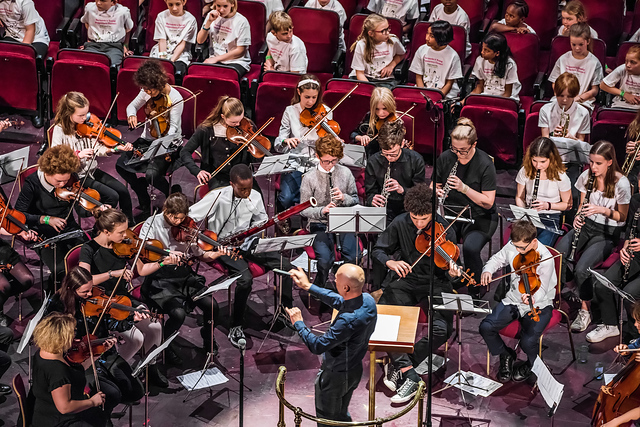 The conductor at the front of the photograph, is facing left and holding a baton in his right hand. He is looking towards members of our orchestra to his left. Further members of the orchestra are seated in front of the conductor and to his right.