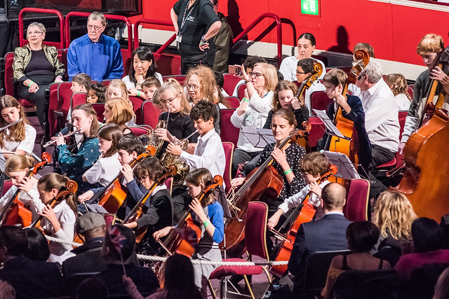 Part of one of our orchestras, with students playing double bass, cello, flute and French horn. An HYOT tutor and some parents and volunteers are amongst the group.