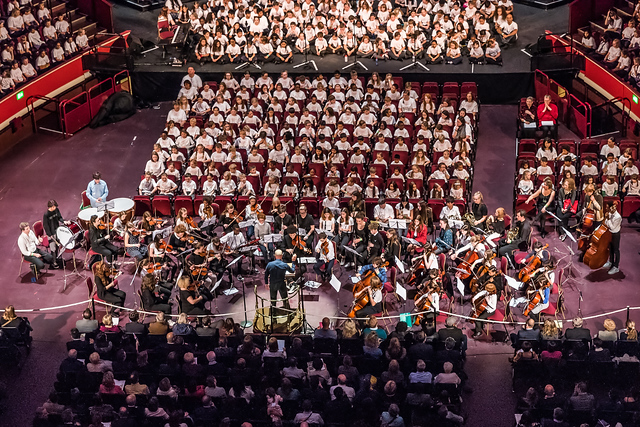 One of HYOT's orchestras are seated in the auditorium, with the conductor standing facing them at the front. Other children and audience members are seated all around them.