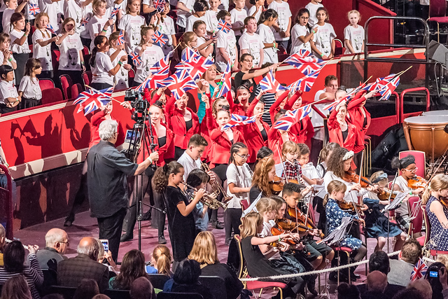 A group of children and young people are standing and waving Union Jack flags. Some of the group are wearing red jackets and behind them is another group wearing white t-shirts. In front are a group of some of the youngest members of our orchestras, seated and playing their instruments.