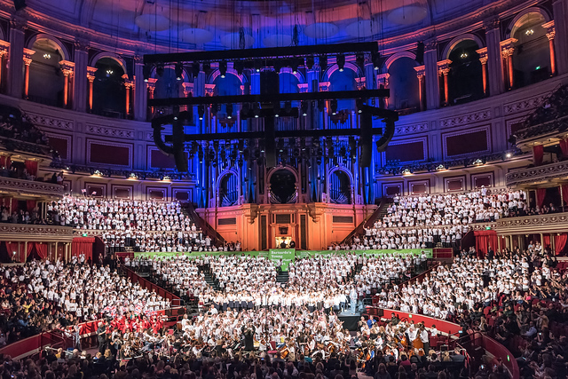 The interior of the Royal Albert Hall showing children wearing white tops, in seating sloping down towards the orchestra at the front. At the back the organ is lit up with blue lighting.