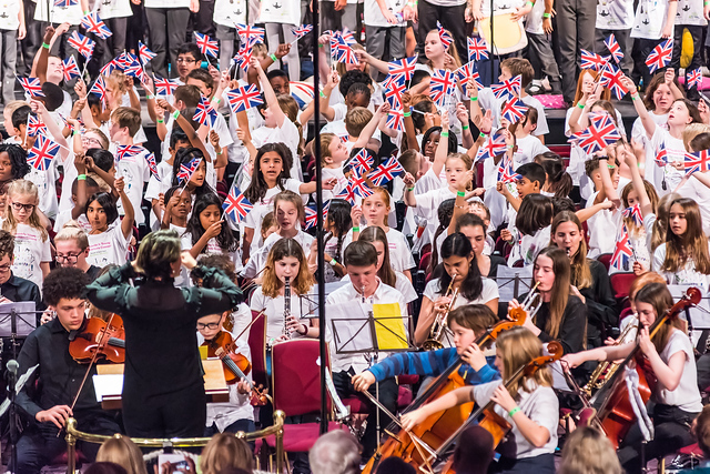 A group of children and young people wearing white tops are waving Union Jack flags. In front of them are members of HYOT's orchestra, with the conductor and some student cellists at the front of the group.