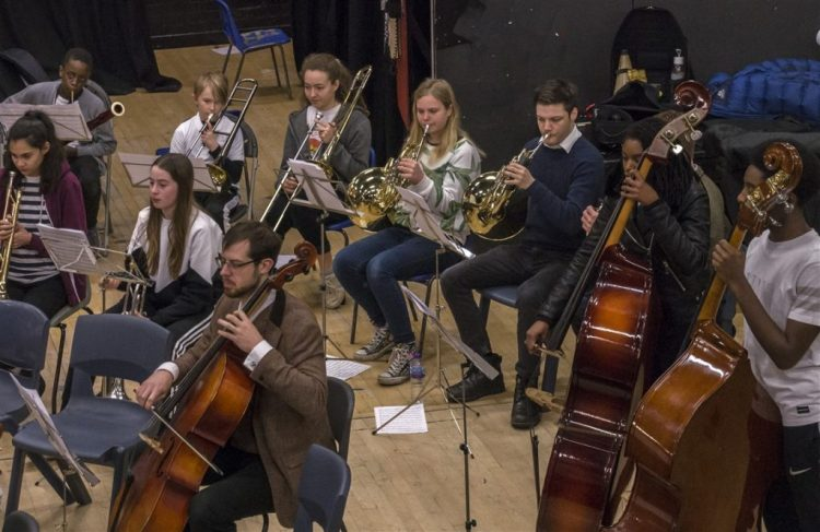 This is a photo of students and two tutors playing in an orchestra at one of our concerts. The musical instruments that they are playing include: bassoon, trumpet, French horn, trombone, cello and double bass.