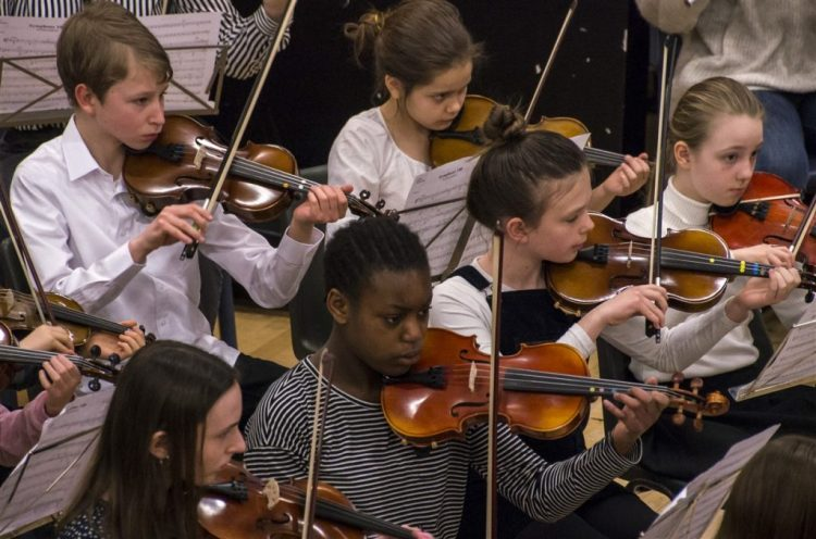 A group of HYOT students playing violins or violas. They are part of an orchestra performing at one of our Saturday School concerts.