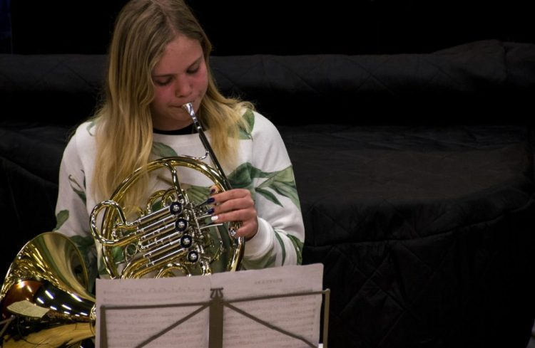 A Saturday school student, playing a solo on French horn at one of our concerts.