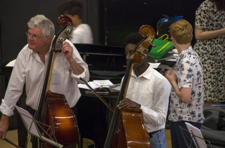 A photograph of a tutor and a student, both getting ready to play double bass in an orchestra at one of our concerts. The tutor is tuning their double bass.
