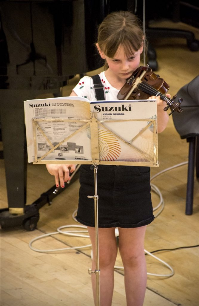A young student playing a solo on violin at a concert. There is a music stand in front of her with a music book saying ' Suzuki Violin School'
