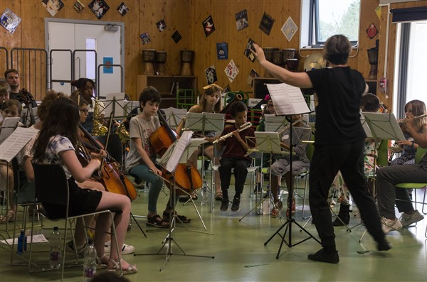The Summer School orchestra, with the conductor in black at the front facing the students. The students are facing us and playing a range of instruments including a flute and cellos.