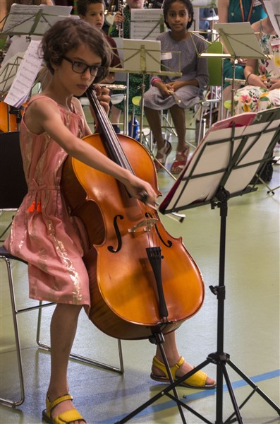 A young student playing a cello, there is a music stand with a music book on it, in front of them. Other students are seated in the background.