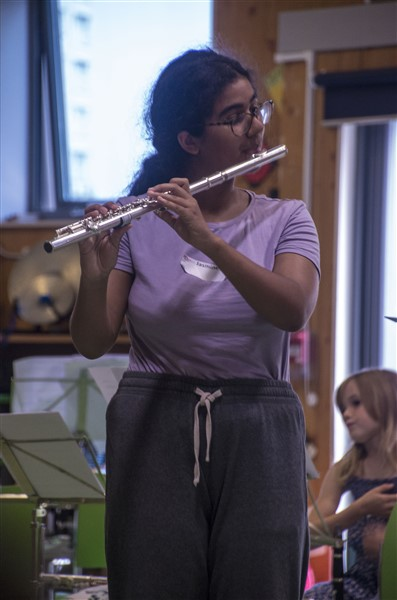 A young person playing a flute solo. They are standing up and are wearing a light purple t-shirt.