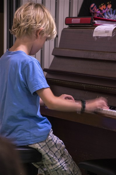 A boy playing a solo on piano. They are seated and wearing a light blue t-shirt.
