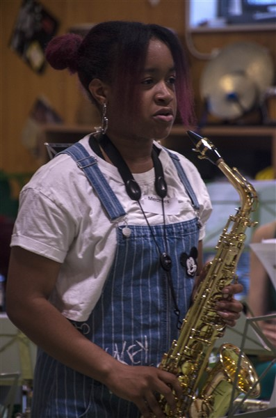 A student who is holding a saxophone, ready to play.