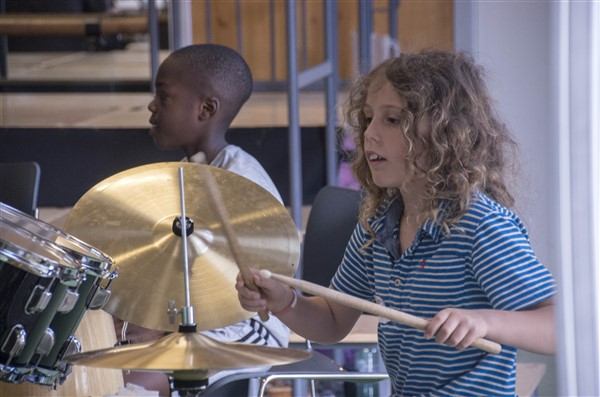 Two young students playing percussion. One of them is holding drum sticks and is playing the cymbals.
