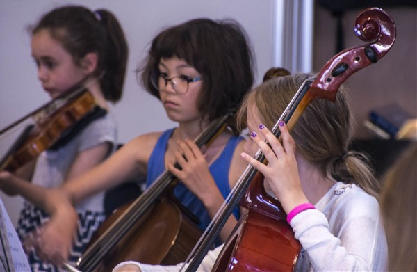 Three girls, one playing a violin and the other two playing cello.