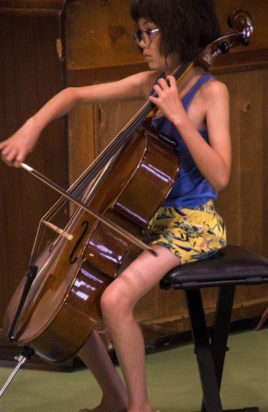 A student sitting on a stool, playing a cello solo.