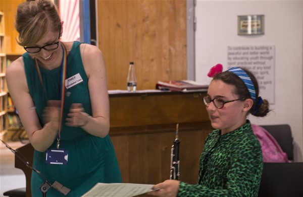 A student and tutor. The tutor is clapping and the students is holding an oboe and smiling and is handing the tutor some music.